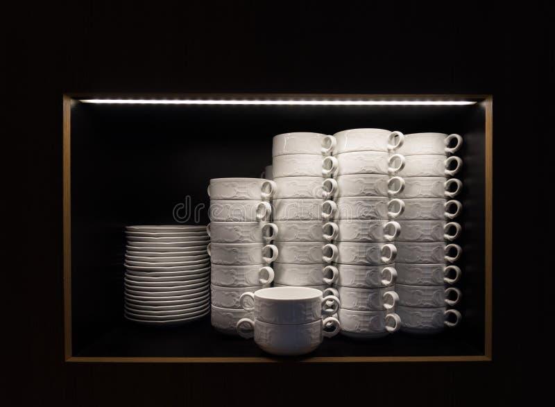 Ρύθμιση των κύπελλων και των πιάτων σούπας σε ένα πλαίσιο με το σκοτεινό υπόβαθρο στοκ φωτογραφίες