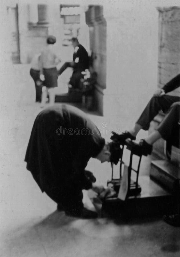 Ρώμη, Ιταλία, 1970 - ένα στιλβωτικό παπουτσιών εκτελεί την εργασία του προσεκτικά στοκ εικόνα