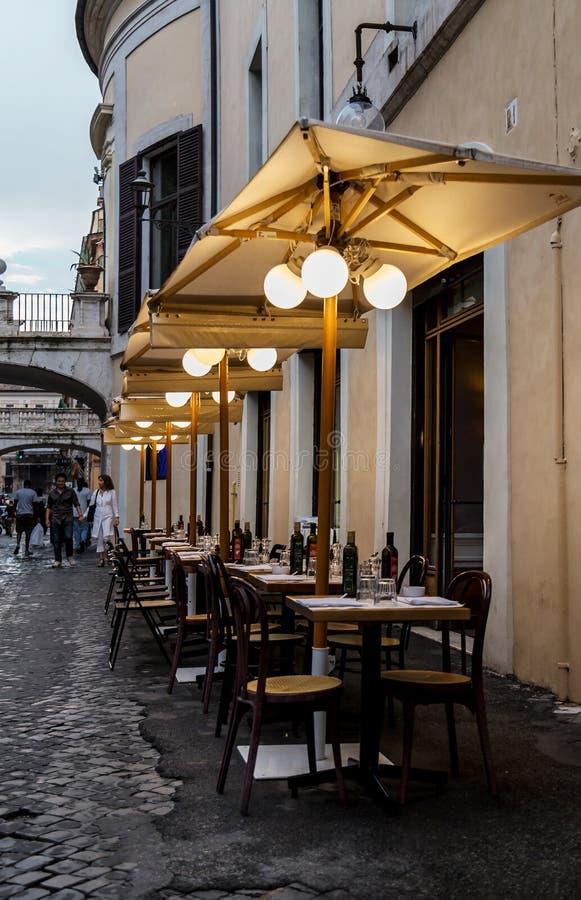 Ρώμη, Ιταλία - 20 Αυγούστου 2018: Χαρακτηριστική παλαιά ρωμαϊκή στενή οδός Καλό πεζοδρόμιο café με τους κενούς πίνακες, τις ομπρέ στοκ εικόνες