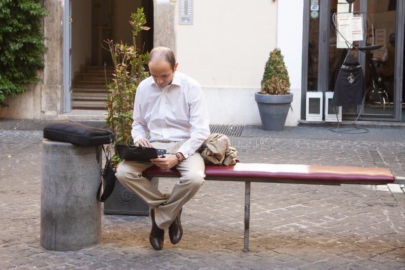 Ρώμη, Ιταλία, στις 14 Οκτωβρίου 2011: Συνεδρίαση νεαρών άνδρων σε έναν πάγκο οδών με ένα lap-top στοκ φωτογραφία με δικαίωμα ελεύθερης χρήσης