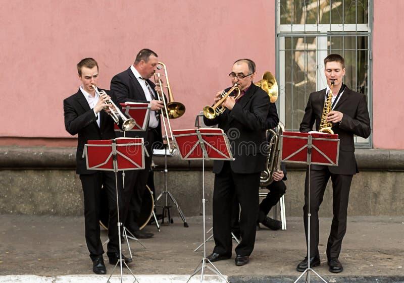 Σάλπιγγα saxophone συνόλων οδών αέρα, ένας εορτασμός ημέρας πόλεων Τέσσερις μουσικοί στο κλασικό μαύρο παιχνίδι κοστουμιών στα όρ στοκ φωτογραφία με δικαίωμα ελεύθερης χρήσης