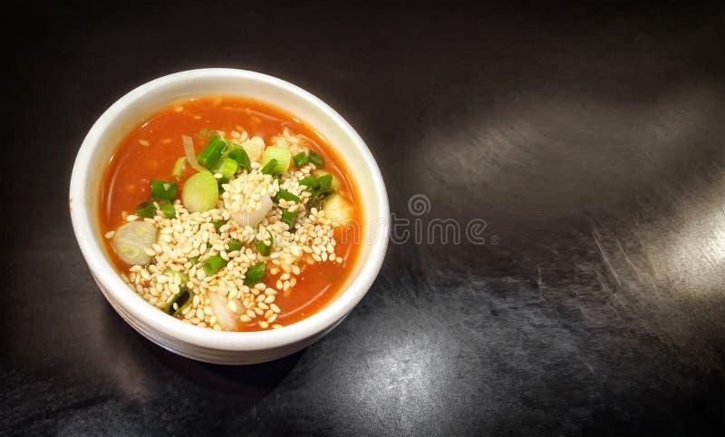 Σάλτσα τσίλι που αναμιγνύεται με το κομματιασμένο σκόρδο, το πράσινο κρεμμύδι και το άσπρο σουσάμι σε ένα πιάτο σε ένα σκοτεινό υ στοκ φωτογραφίες με δικαίωμα ελεύθερης χρήσης