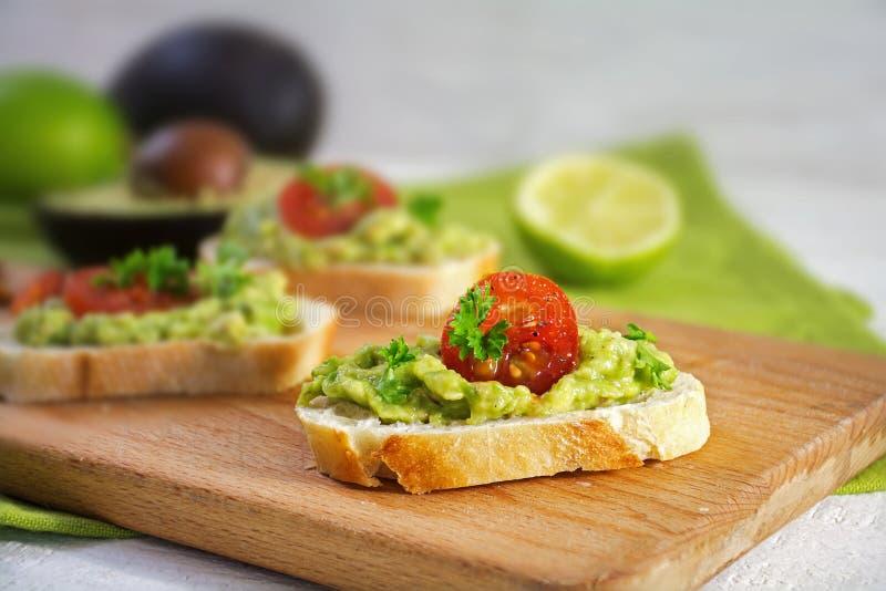 Σάντουιτς καναπεδάκια με την κρέμα ή guacamole και τις ντομάτες αβοκάντο fre στοκ φωτογραφία με δικαίωμα ελεύθερης χρήσης