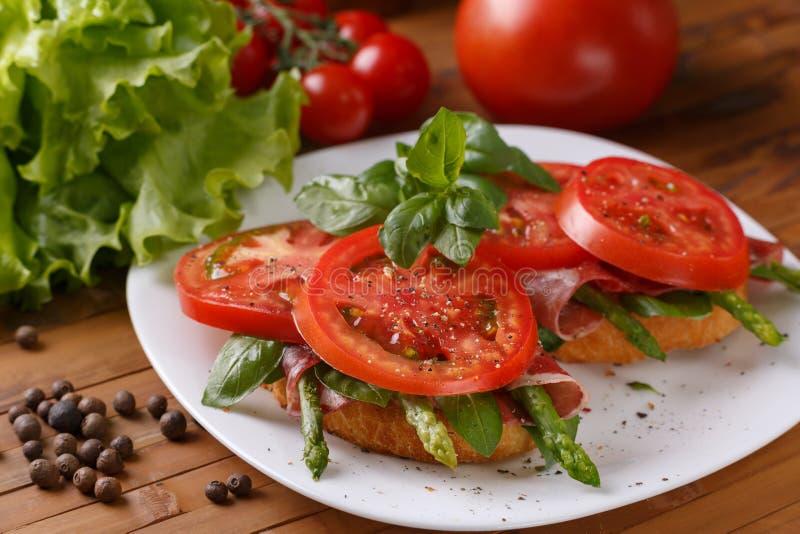Σάντουιτς με τα λαχανικά και ένα jamon σε ένα άσπρο πιάτο στοκ εικόνα με δικαίωμα ελεύθερης χρήσης