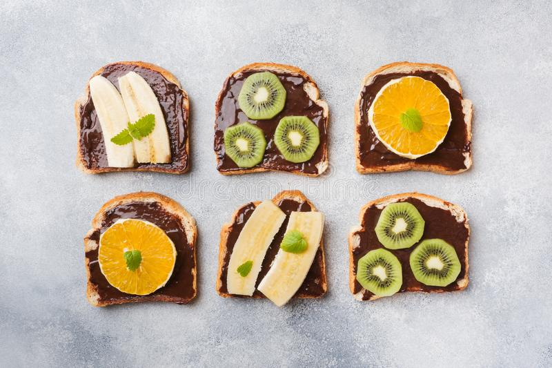 Σάντουιτς με την κόλλα σοκολάτας και διάφορα φρούτα σε έναν γκρίζο πίνακα r Εύγευστο πρόγευμα έννοιας στοκ εικόνες