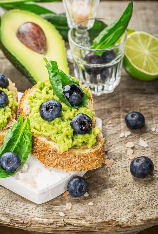 Σάντουιτς με το αβοκάντο, τα βακκίνια και το σπανάκι στοκ εικόνες