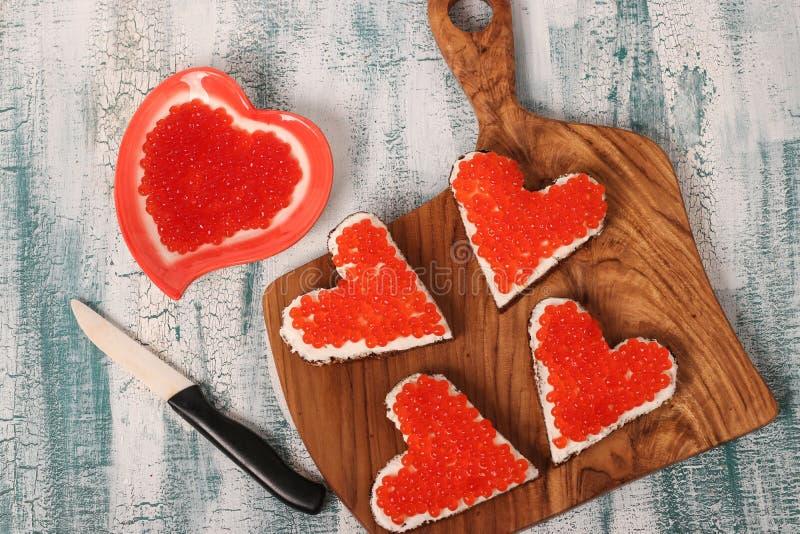 Σάντουιτς με το κόκκινο τυρί χαβιαριών και κρέμας με μορφή μιας καρδιάς για την ημέρα του βαλεντίνου στοκ εικόνα με δικαίωμα ελεύθερης χρήσης