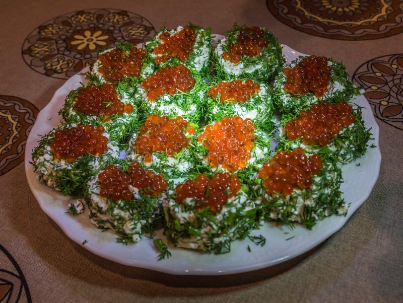 Σάντουιτς με το κόκκινο χαβιάρι και πράσινα σε ένα πιάτο στοκ εικόνα