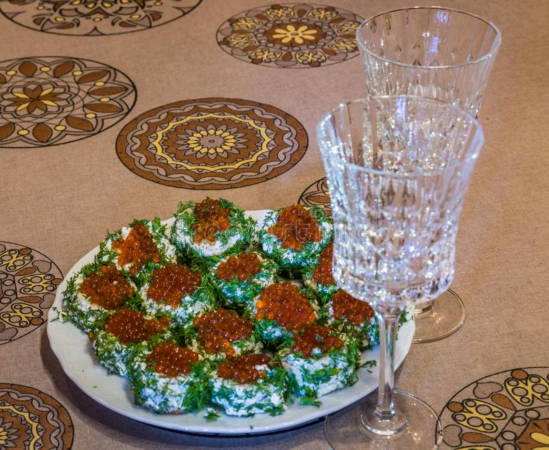 Σάντουιτς με το κόκκινο χαβιάρι και πράσινα σε πιάτο και δύο γυαλιά στοκ εικόνες με δικαίωμα ελεύθερης χρήσης
