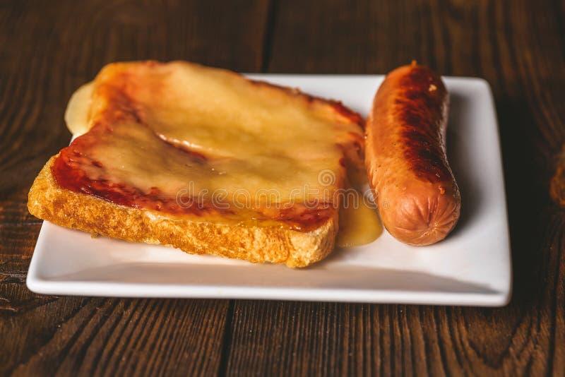 Σάντουιτς με το λειωμένο τυρί και τηγανισμένη κινηματογράφηση σε πρώτο πλάνο λουκάνικων στα πλαίσια ενός σκοτεινού δέντρου στοκ εικόνες με δικαίωμα ελεύθερης χρήσης