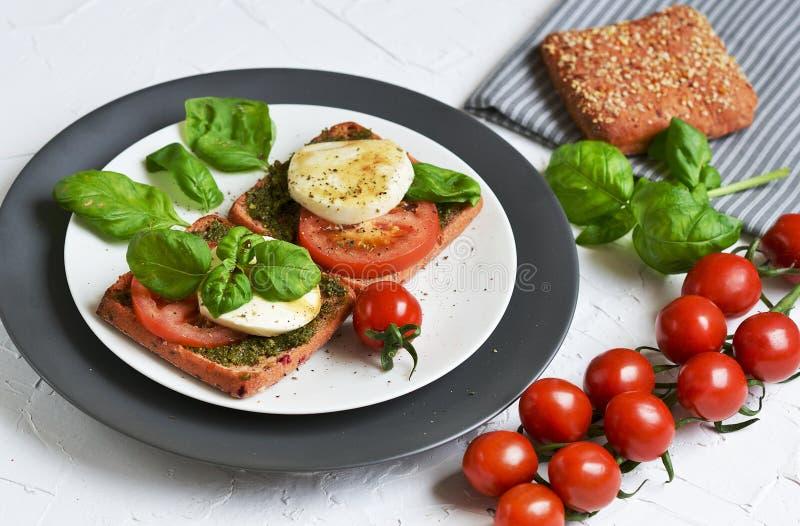 Σάντουιτς με το τυρί μοτσαρελών και τις κόκκινες ντομάτες στοκ εικόνα