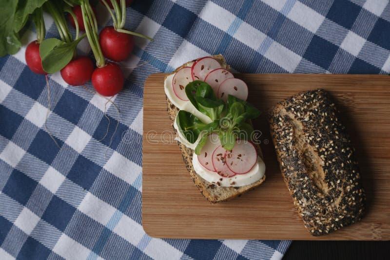 Σάντουιτς με το τυρί mozarella και ραδίκι φετών στον ξύλινο καφετή τέμνοντα πίνακα στοκ φωτογραφίες