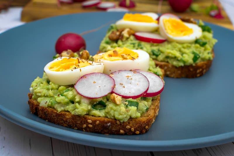Σάντουιτς με το φρέσκο ραδίκι αβοκάντο guacamole και το βρασμένο αυγό στοκ εικόνα