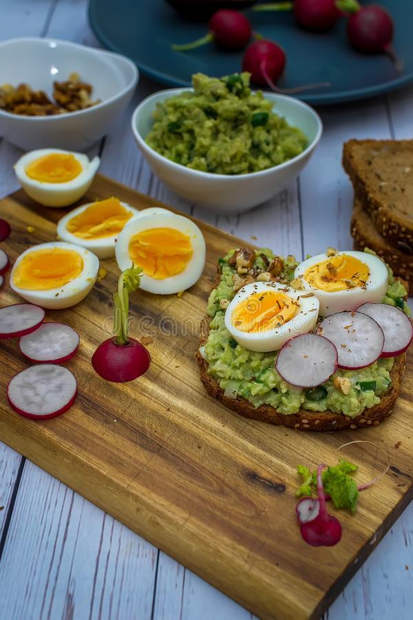 Σάντουιτς με το φρέσκο ραδίκι αβοκάντο guacamole και το βρασμένο αυγό στοκ εικόνες