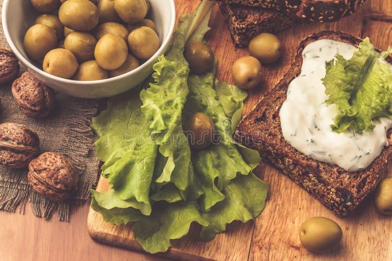 Σάντουιτς του σπιτικού ψωμιού με τη σάλτσα τυριών ή την κρέμα, μαρούλι, ξύλα καρυδιάς, ελιά στοκ εικόνες με δικαίωμα ελεύθερης χρήσης