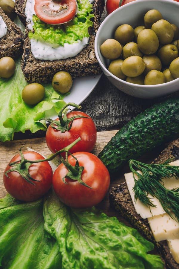 Σάντουιτς του σπιτικού ψωμιού με τη σάλτσα τυριών ή την κρέμα, μαρούλι, ξύλα καρυδιάς, ελιά στοκ φωτογραφία