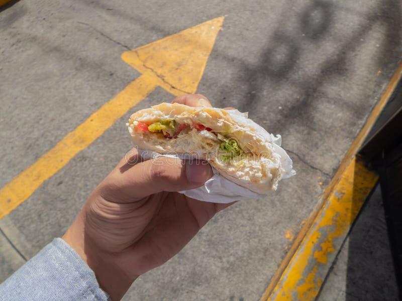 σάντουιτς ψωμιού εκμετάλλευσης χεριών ατόμων τροφίμων οδών με το hamm και letucce στοκ εικόνα με δικαίωμα ελεύθερης χρήσης
