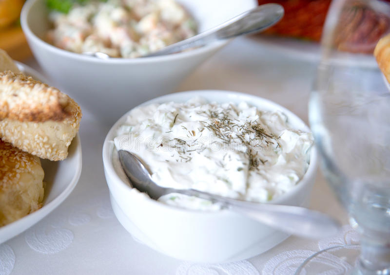 Σάλτσα Tzatziki Ελληνική εμβύθιση αγγουριών γιαουρτιού στο άσπρο κύπελλο πέρα από τον πίνακα στοκ φωτογραφία