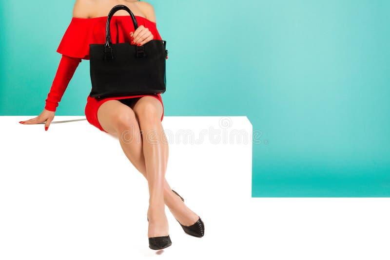 Σέξι γυναίκα με ψηλά τακούνια με μαύρη τσάντα σε μπλε φόντο στοκ εικόνα με δικαίωμα ελεύθερης χρήσης