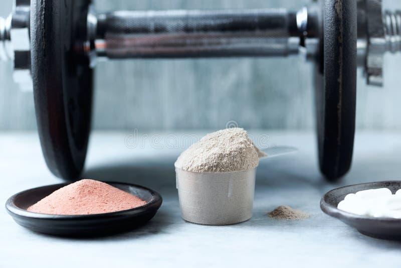 Σέσουλα της πρωτεΐνης ορρού γάλακτος, των καψών βήτα-αλανινών, της σκόνης κρεατίνης και ενός αλτήρα στο υπόβαθρο στοκ εικόνα με δικαίωμα ελεύθερης χρήσης