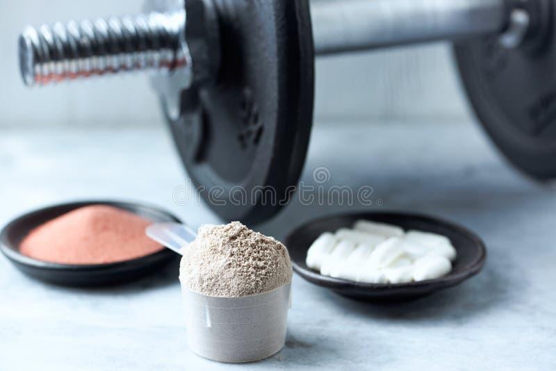 Σέσουλα της πρωτεΐνης ορρού γάλακτος, των καψών βήτα-αλανινών, της σκόνης κρεατίνης και ενός αλτήρα στο υπόβαθρο στοκ φωτογραφία με δικαίωμα ελεύθερης χρήσης
