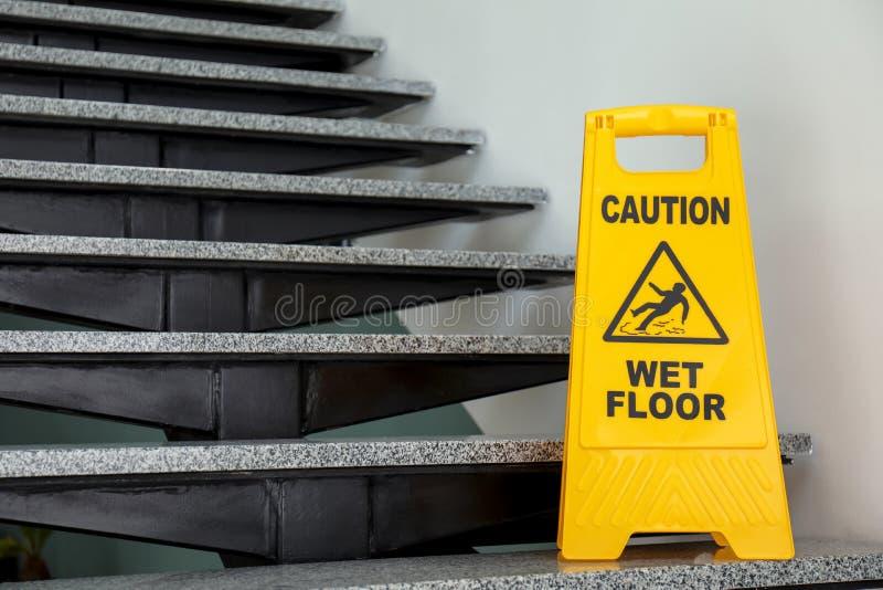 Σήμανση ασφάλειας με το υγρό πάτωμα προσοχής φράσης στα σκαλοπάτια στοκ εικόνες