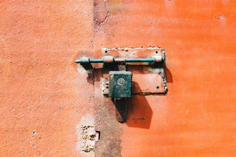 Σίδηρος, πορτοκαλιά σκουριασμένη πόρτα μετάλλων με την κλειδαριά και παραθυρόφυλλο στοκ φωτογραφίες με δικαίωμα ελεύθερης χρήσης