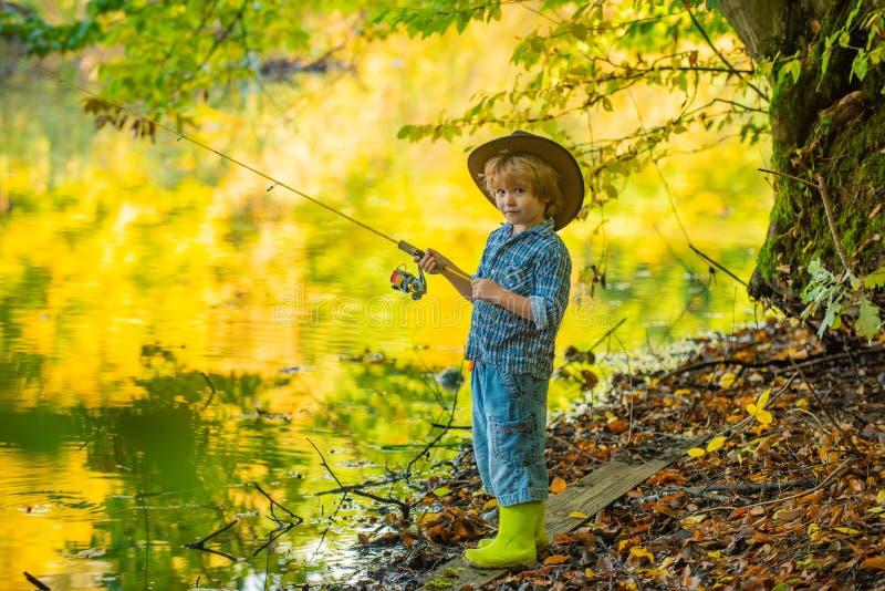 Σαββατοκύριακο Ένα ψαράκι ψαρεύει σε μια λίμνη Ένα όμορφο αγόρι και τα χόμπι του Καλάμι ψαρέματος Κατασκήνωση με παιδιά Ψάρια στοκ φωτογραφίες