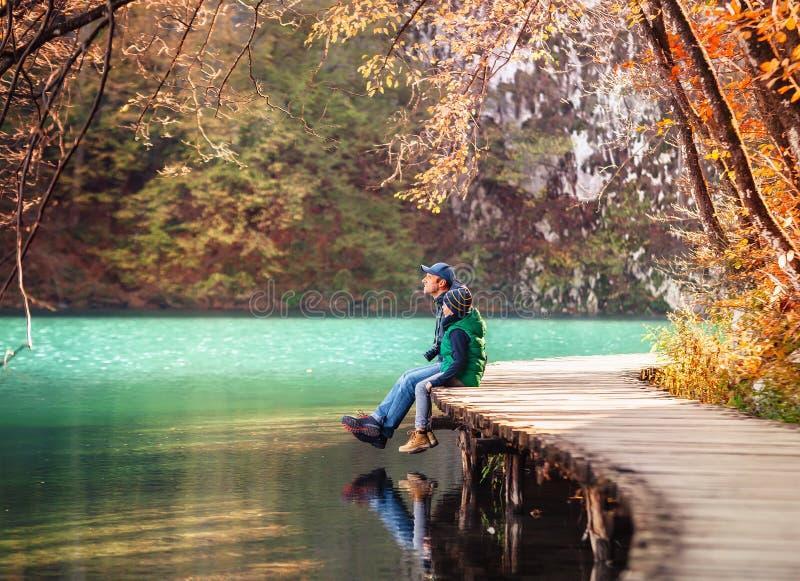 Σαββατοκύριακο στο πάρκο 0 φθινοπώρου ο πατέρας με το γιο κάθεται στη γέφυρα κοντά στοκ εικόνες