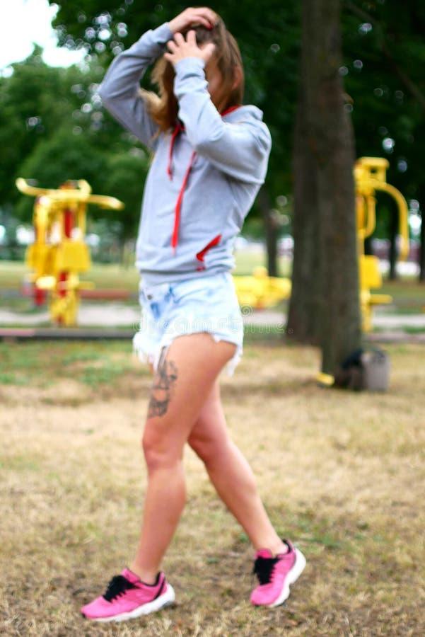 Σαγηνευτική νέα γυναίκα στα κοντά σορτς τζιν Προκλητικό photosession στο πάρκο στοκ εικόνα με δικαίωμα ελεύθερης χρήσης