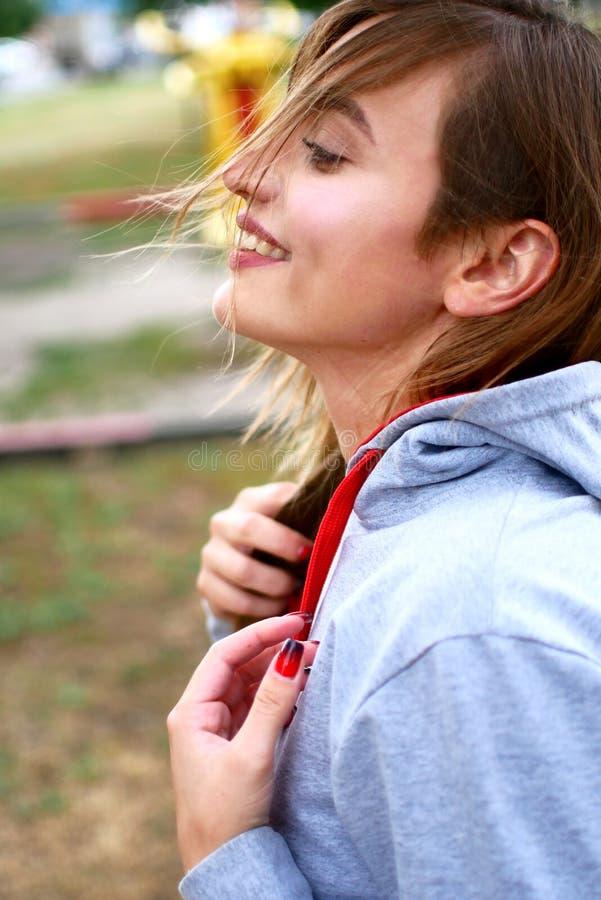 Σαγηνευτική νέα γυναίκα στα κοντά σορτς τζιν Προκλητικό photosession στο πάρκο στοκ φωτογραφία