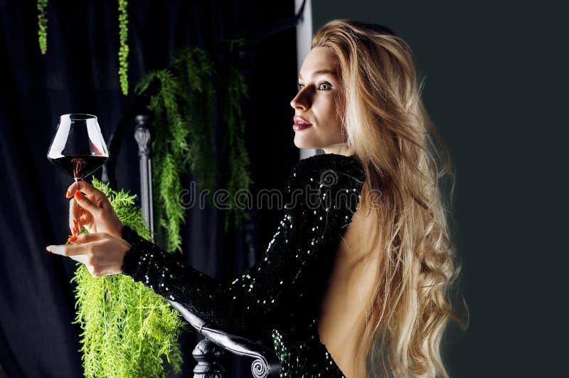 Σαγηνευτικός ξανθός σε μια πράσινη τοποθέτηση φορεμάτων βραδιού με ένα ποτήρι του κόκκινου κρασιού στοκ εικόνα