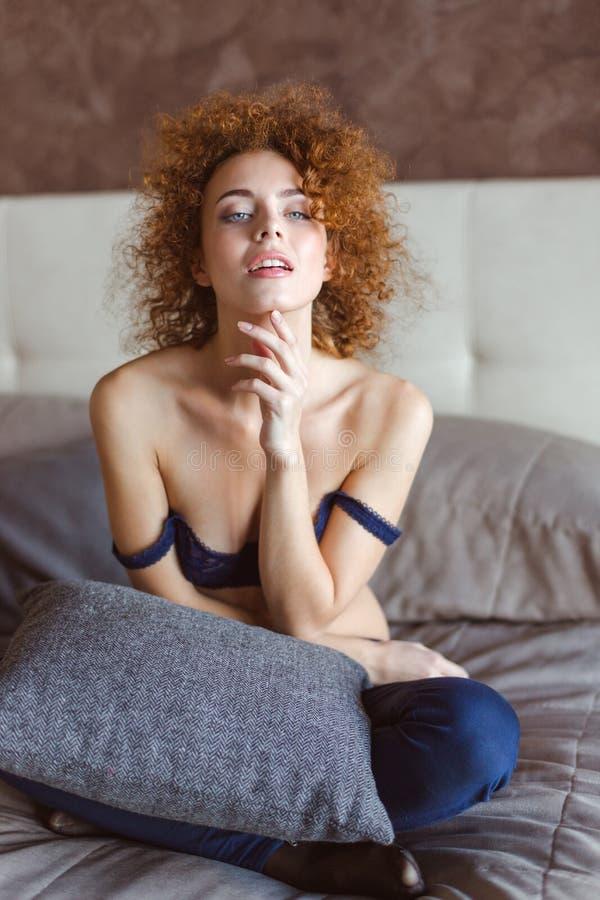 Σαγηνευτικό τρυφερό θηλυκό με τη σγουρή κόκκινη συνεδρίαση τρίχας στο κρεβάτι στοκ εικόνες