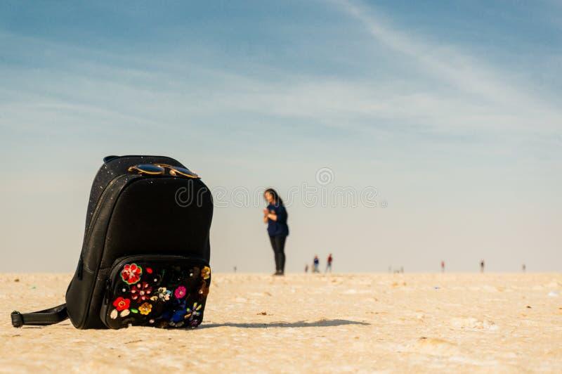 σακίδιο πλάτης που τοποθετείται στην άσπρη αλατισμένη άμμο του rann του kutchh με ένα ινδικό κορίτσι που στέκεται στην απόσταση στοκ φωτογραφίες