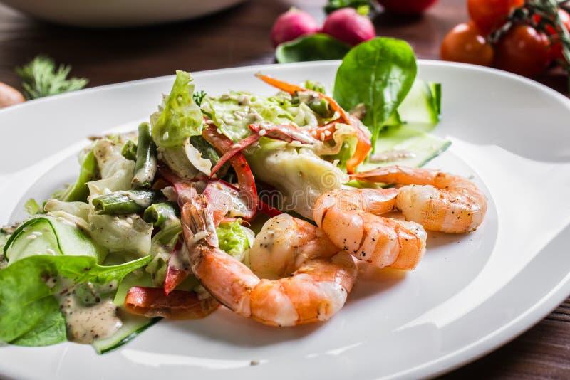 Σαλάτα από τα πράσινα και γαρίδες σε ένα άσπρο κεραμικό πιάτο στοκ εικόνες
