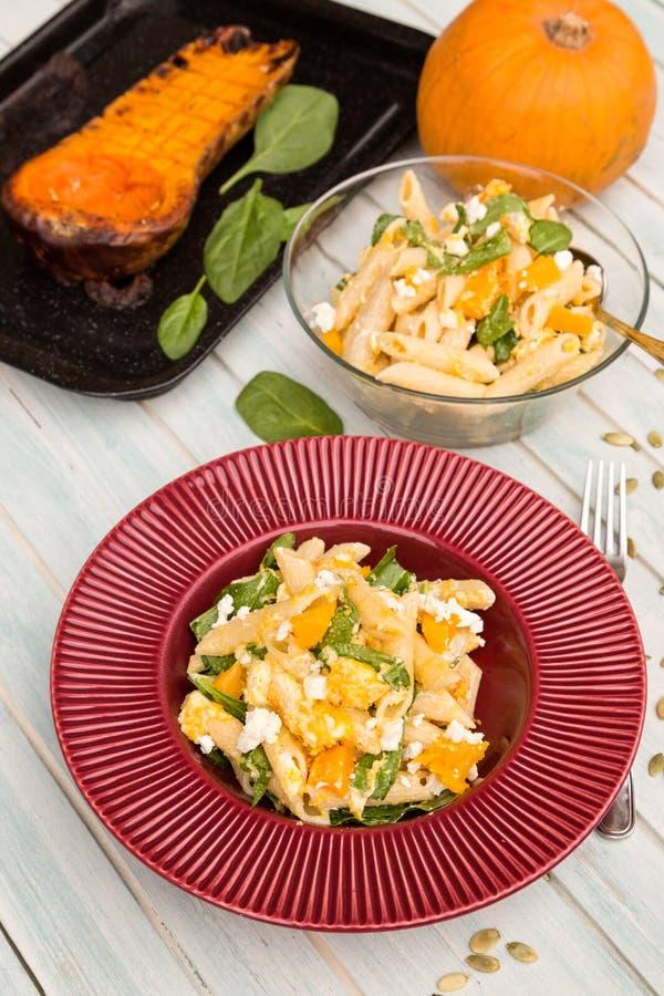 Σαλάτα ζυμαρικών με την ώριμη κολοκύθα, το τυρί αιγών και το σπανάκι μωρών στοκ εικόνες με δικαίωμα ελεύθερης χρήσης