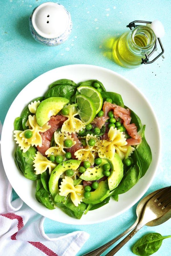 Σαλάτα ζυμαρικών με το σπανάκι, το αβοκάντο, τον αλατισμένους σολομό και το πράσινο μπιζέλι κορυφή στοκ φωτογραφίες