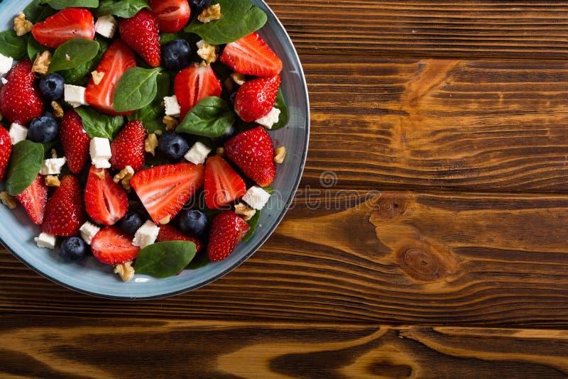 Σαλάτα θερινών φραουλών με το σπανάκι, το τυρί, τα καρύδια και το βακκίνιο στοκ φωτογραφία