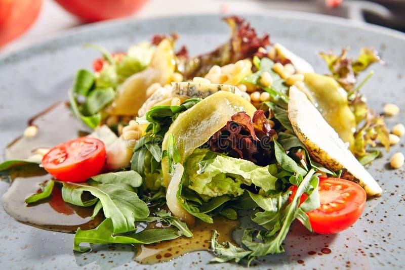 Σαλάτα με τα τεμαχισμένα αχλάδια, gorgonzola το τυρί, τα πράσινα και τα καρύδια πεύκων στοκ εικόνες