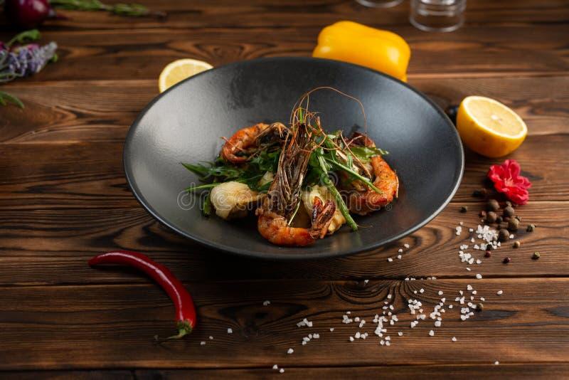 σαλάτα με τις ψημένες στη σχάρα γαρίδες και τα τριζάτα λαχανικά σε ένα πιάτο σε ένα ξύλινο υπόβαθρο στοκ φωτογραφία με δικαίωμα ελεύθερης χρήσης