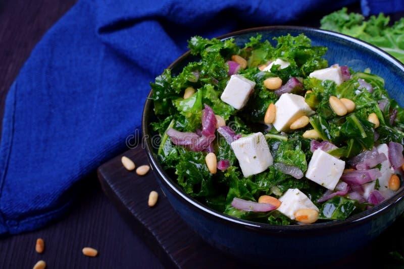 Σαλάτα με το κατσαρό λάχανο, το κόκκινο κρεμμύδι, το τυρί φέτας και τα καρύδια πεύκων στοκ εικόνα