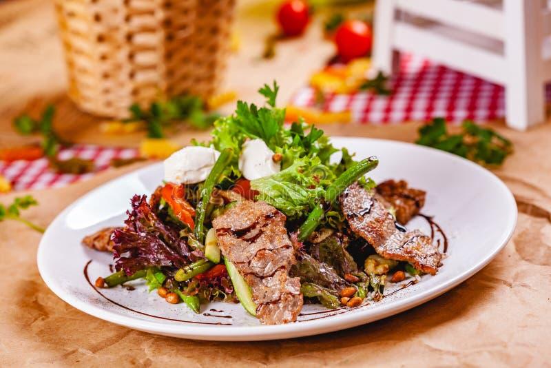 Σαλάτα με το τηγανισμένο κρέας, τα καρύδια πεύκων, τα λαχανικά και το τυρί μοτσαρελών στο άσπρο πιάτο στοκ φωτογραφία με δικαίωμα ελεύθερης χρήσης