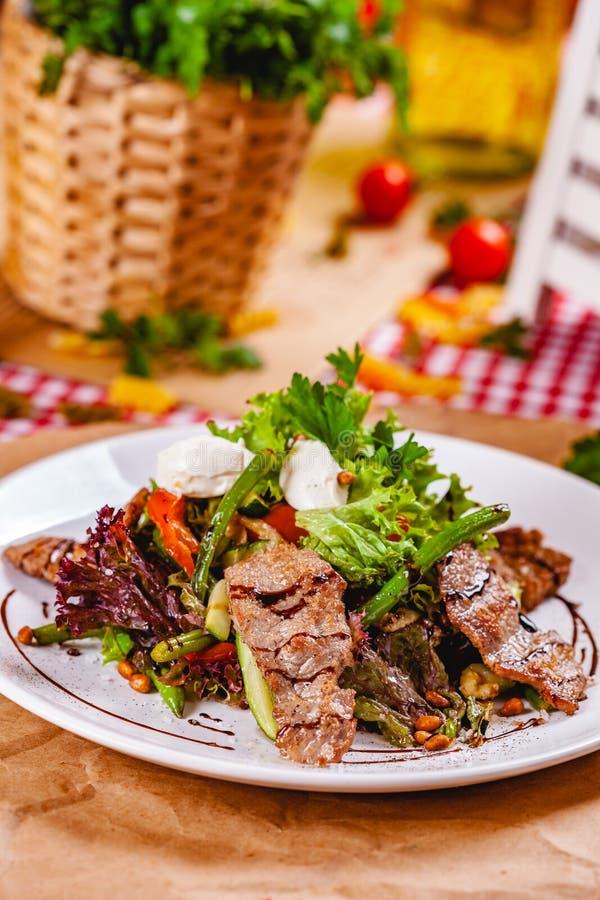Σαλάτα με το τηγανισμένο κρέας, τα καρύδια πεύκων, τα λαχανικά και το τυρί μοτσαρελών στο άσπρο πιάτο στοκ εικόνα