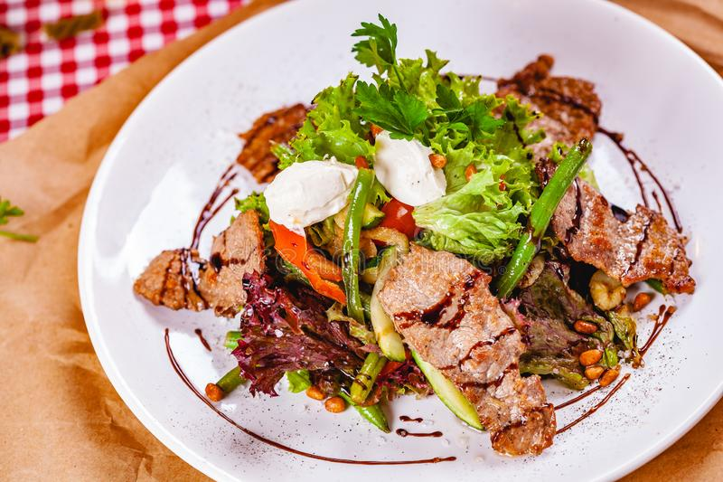 Σαλάτα με το τηγανισμένο κρέας, τα καρύδια πεύκων, τα λαχανικά και το τυρί μοτσαρελών στο άσπρο πιάτο στοκ φωτογραφίες με δικαίωμα ελεύθερης χρήσης
