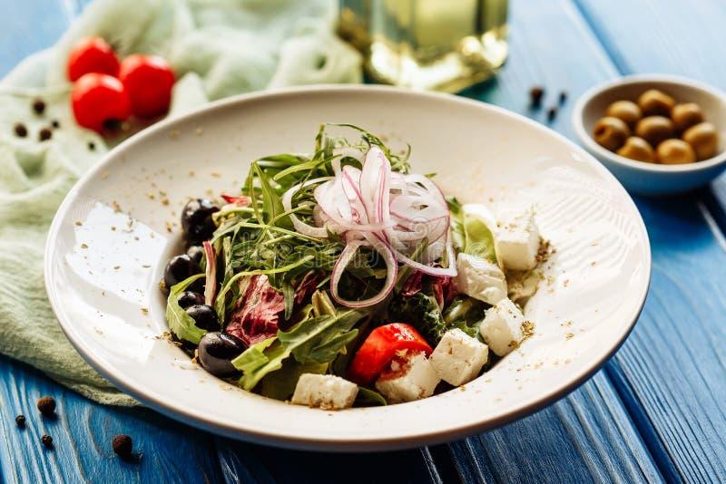 Σαλάτα με το arugula, την ντομάτα, το τυρί και το κόκκινο κρεμμύδι Ολόκληρη άποψη πιάτων στοκ φωτογραφίες