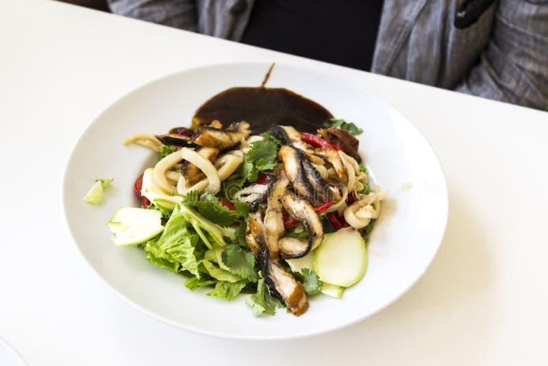 Σαλάτα με το cilantro και τηγανισμένες μελιτζάνες σε ένα άσπρο πιάτο σε έναν άσπρο πίνακα Στο υπόβαθρο είναι ένας ανθρώπινος αριθ στοκ εικόνες