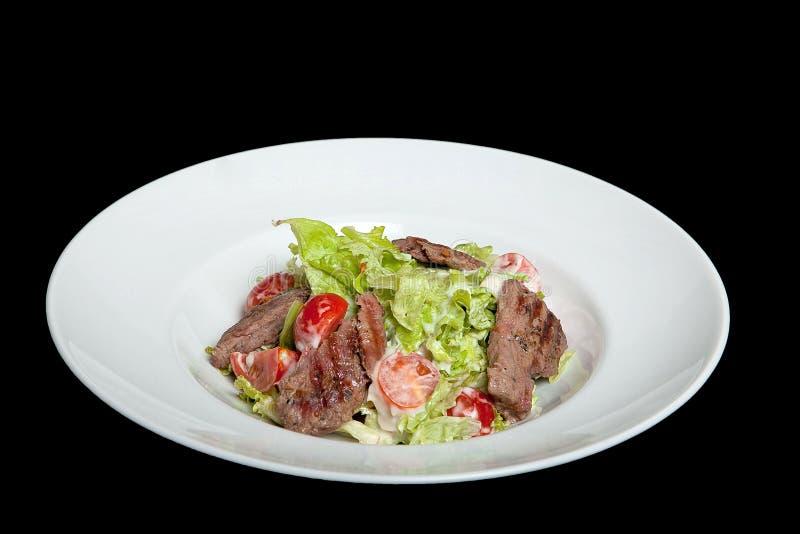 Σαλάτα μοσχαρίσιων κρεάτων, σαλάτα με τις μεγάλες φέτες του μοσχαρίσιου κρέατος και φρέσκα λαχανικά σε ένα πιάτο σε ένα μαύρο υπό στοκ φωτογραφίες