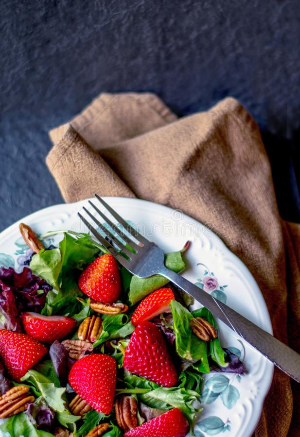 Σαλάτα πεκάν και φραουλών με τα μικτά πράσινα στοκ εικόνες