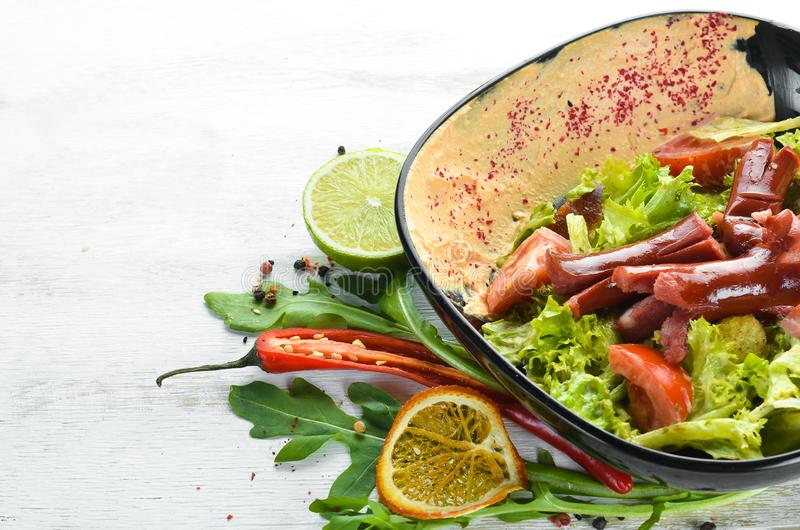 Σαλάτα των φρέσκων λαχανικών και των λουκάνικων σε ένα μαύρο πιάτο E στοκ φωτογραφία με δικαίωμα ελεύθερης χρήσης
