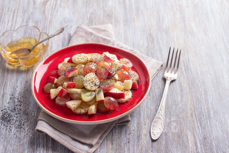 Σαλάτα φρούτων των σταφυλιών, των μπανανών και των μήλων με τους σπόρους και το μέλι παπαρουνών στοκ φωτογραφία με δικαίωμα ελεύθερης χρήσης